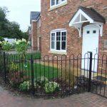 Black bow top metal railings around house