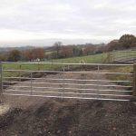 Large Metal Gate on Dirt Road Through Field