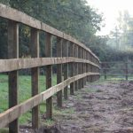 Wooden post and rail fence in muddy field